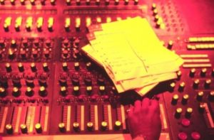 photo taken over the head of Stan Ross of his hand on the recording console