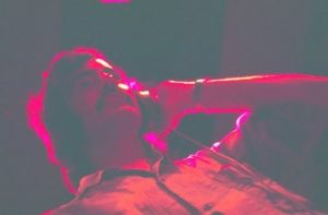 image of Brian Gundy recording a lead vocal inside Gold Star Studios with a red light shining on his head